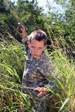pretend: boy in camo raising arm to throw (pretend) grenade