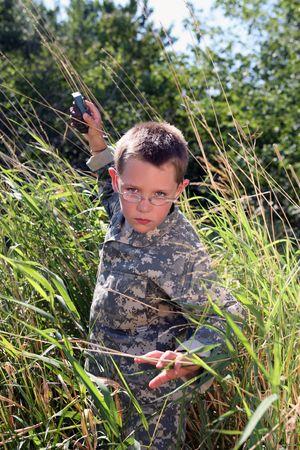 boy in camo raising arm to throw (pretend) grenade
