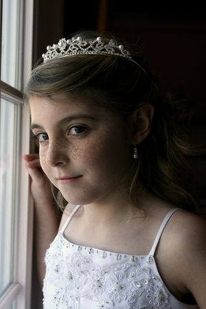 pretty dressed up girl with freckles standing in natural light at the window Stock Photo - 4259778