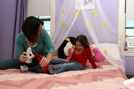 mother taking off her little girl's shoe one the bed