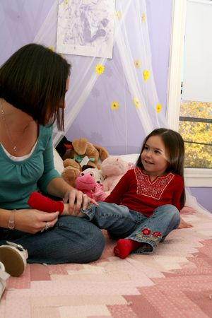 girl socks: 母の彼女の小さな女の子の靴下を削除して、ベッドの上に座って
