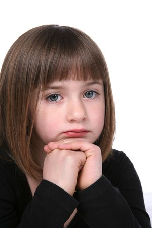 close up of cute girls thoughtful or sad face with chin on her folded hands photo