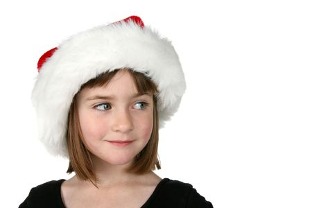 cute girl in Santa hat, looking to the side at the copy space available