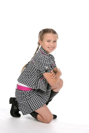 knee bend: fashionable girl kneeling and smiling with arms crossed