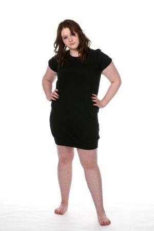 mujer gorda: adolescente con sobrepeso en el corto vestido negro y pies descalzos Foto de archivo