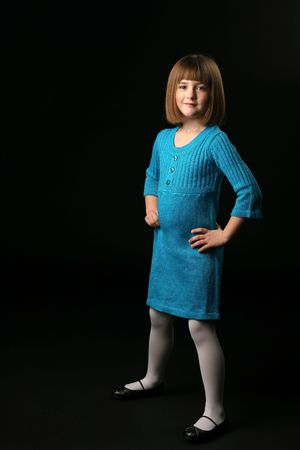 attitude girls: young girl in blue dress standing with her hands on her hips Stock Photo