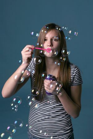 irridescent: pretty teenage girl blowing bubbles Stock Photo