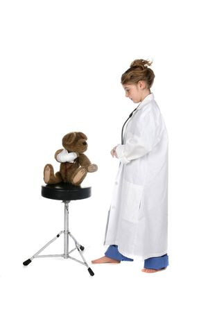 cure girl in medical scrubs attending to a teddy bear with injured arm Stock Photo - 4438020