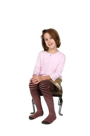 young girl in funky outfit sitting on stool and smiling