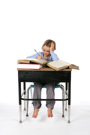 girl at school desk taking notes from large books photo