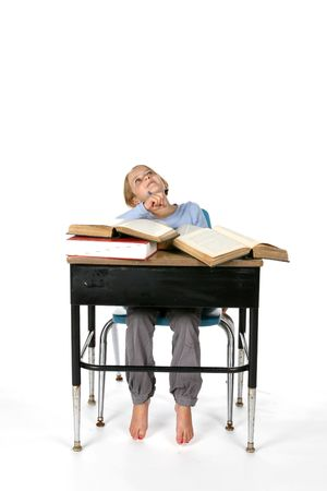 young girl with large books on her school desk photo