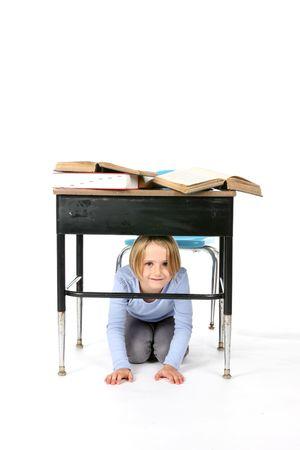 young girl hiding under her school desk photo