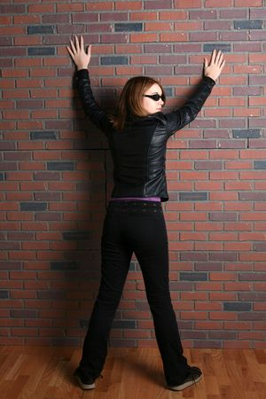 spread legs: teenage girl in black with arms and legs spread against a brick wall Stock Photo