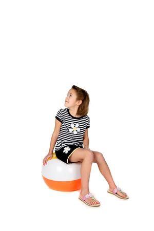 cute girl in skirt sitting on beach ball photo