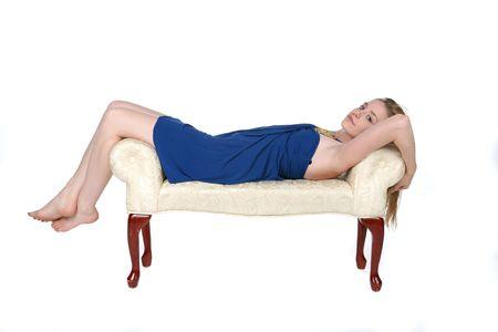 beautiful young woman reclining on white studio bench photo