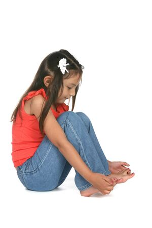 long feet: pretty little girl looking at her bare toes Stock Photo