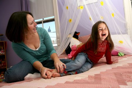 mother tickling her little girl's bare feet on her bed