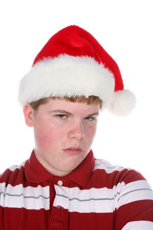 grouchy: teenage boy looking unhappy to be wearing santa hat Stock Photo