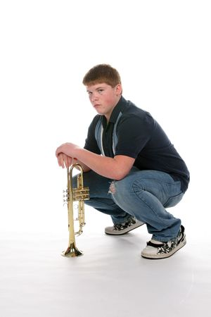 teenage boy leaning on upright trumpet