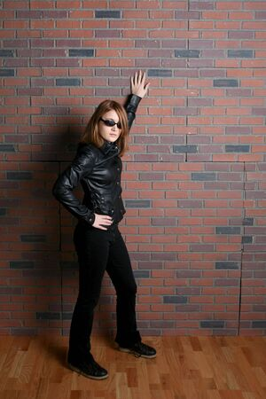 chic: tough looking biker chic leaning against brick wall