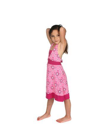 mooi jong meisje in roze jurk en blote voeten Stockfoto
