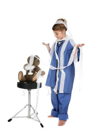 cute girl in blue scrubs, teddy bear, and gauze Stock Photo - 5089364
