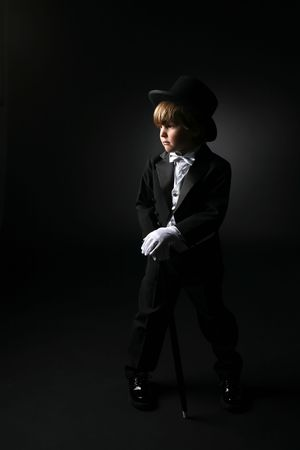 cute young boy wearing tuxedo and gloves photo