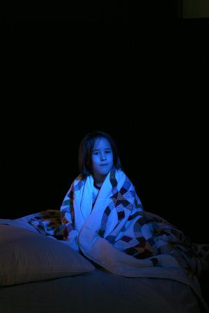 girl in the dark on a bed wrapped in quilt photo