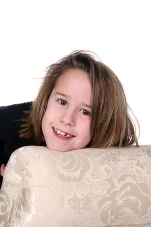 pretty young girl with missing tooth leaning on couch photo