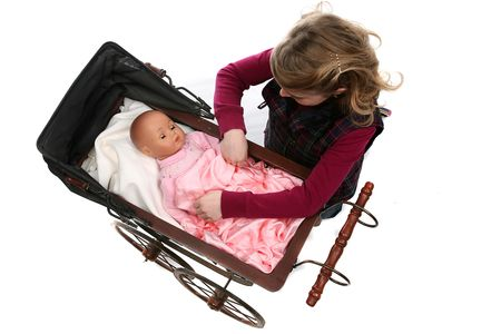 role play: young girl looking down at doll in antique baby carriage