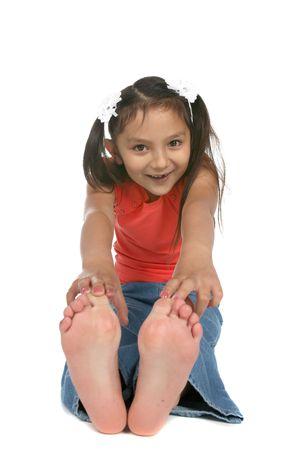 うち、つま先に触れるフィートで座っている女の子
