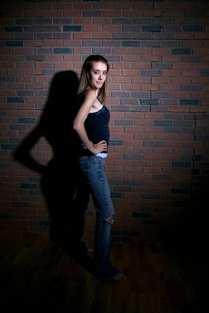 anorexia girl: pretty thin teenage girl standing next to brick wall