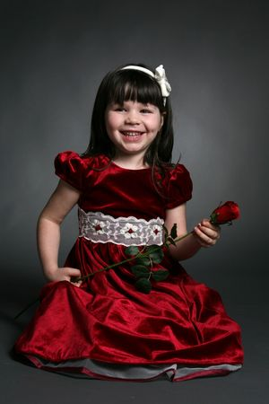 dark haired little girl in red dress with rose Stock Photo - 7873984