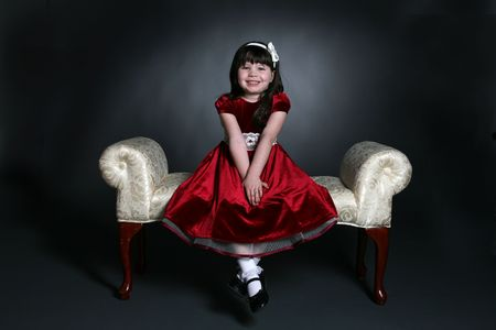 pretty little girl sitting on bench in red holiday dress photo