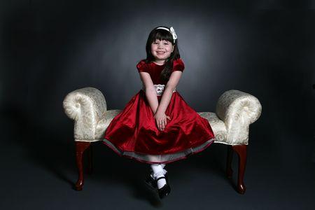velvet dress: pretty little girl sitting on bench in red holiday dress Stock Photo
