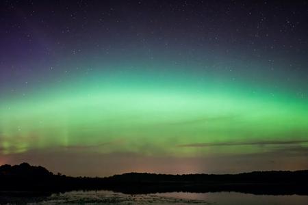 morado: Luces del Norte, Aurora boreal que muestra sobre un lago en Wisconsin. Foto de archivo