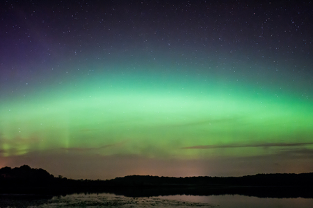 Northern Lights, Aurora Borealis displaying over a lake in Wisconsin. Stock Photo