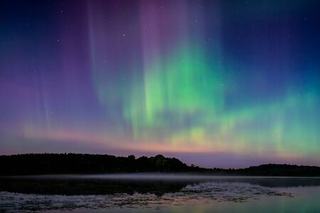 The northern lights, aurora borealis over a lake in Wisconsin. Stock Photo