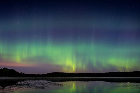 The northern lights, aurora borealis over a lake in Wisconsin. Фото со стока