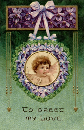 A vintage Valentines postcard with a cherub holding a love letter in a garland of violets photo