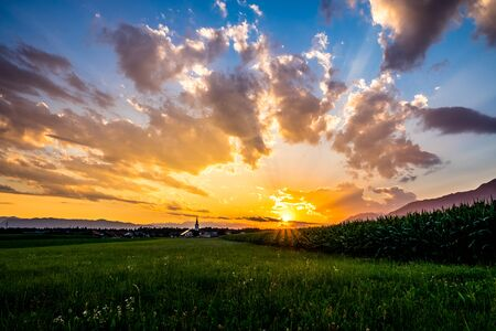 Sunset in the countryside - dramatic sky with clouds, green meadow and cornfield, houses with church, and mountains on background