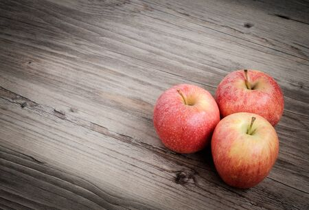 Three fresh apples on table with wooden background