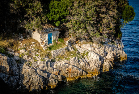 Small old stone lodge on a rocky shore close to a lake, river or sea. Small shed with closed blue door. Next to the dense forest.