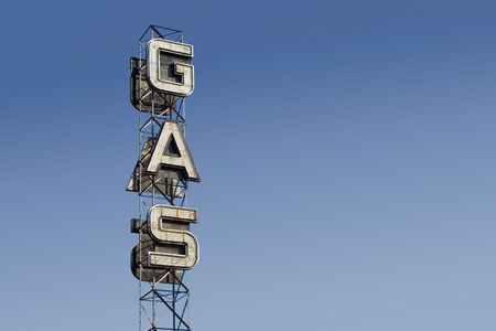 combust: An industrial looking sign for a gas station against the blue sky.