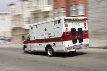 ambulance car: An ambulance blazes by, its sirens whaling.  An intensional camera blur gives a feeling of a rushed tension to the scene.