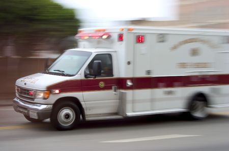 blazes: An ambulance blazes by, its sirens whaling.  An intentional camera blur gives a feeling of a rushed tension to the scene.