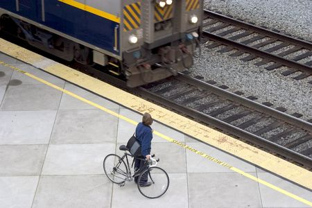 A commuter waits with her bike for the arriving train. Imagens