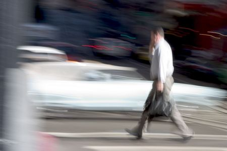 multitask: A business man walks across the street briskly while talking on a cell phone.  An intensionally long shutter gives a blurred sense of urgency to the scene. Stock Photo