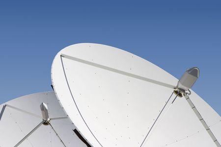 Two satellite dishes point skyward. Banco de Imagens