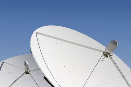 teleconference: Two satellite dishes point skyward. Stock Photo
